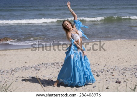 Belly dancer in blue costume on the beach  - stock photo