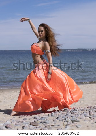 Belly dancer in bright costume on the beach  - stock photo