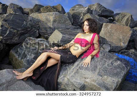 Belly dancer on the rocks stock image - stock photo