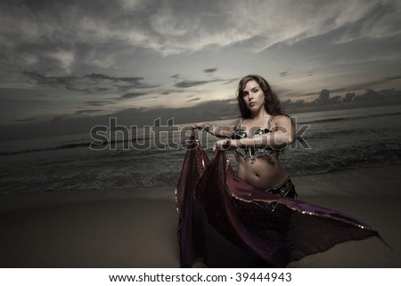 Belly dancer on the sand with a purple veil - stock photo