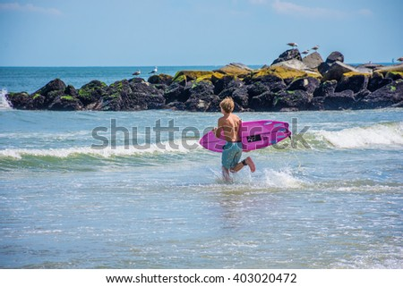 BELMAR, NEW JERSEY-AUGUST 1 - A boy runs into the surf on a beautiful Summer day on August 1 2015 in Belmar New Jersey. - stock photo