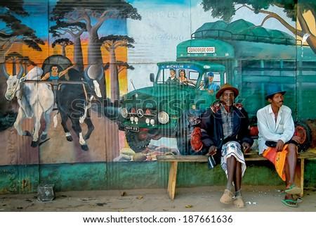 BELO SUR TSIRIBIHINA, MADAGASCAR, SEPT 15:  Unidentified elderly men sitting in front of a mural on sept 15, 2004 in Belo Tsiribihina, west of Madagascar - stock photo