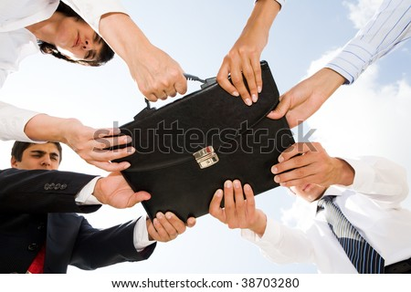 Below angle of people hands holding black leather briefcase simultaneously