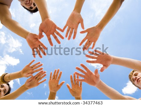 Below angle of several teens keeping their hands in air in the form of circle - stock photo