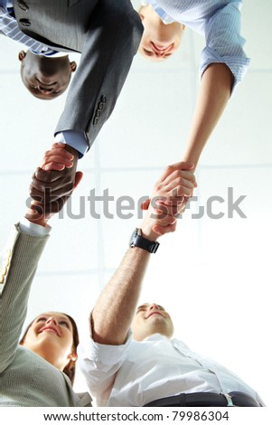 Below angle of two pairs of successful associates handshaking - stock photo