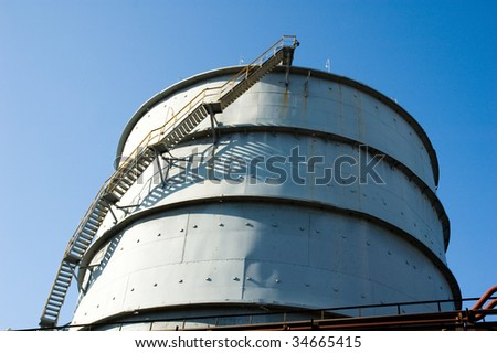 Below shot of big modern plant pipe with blue sky above