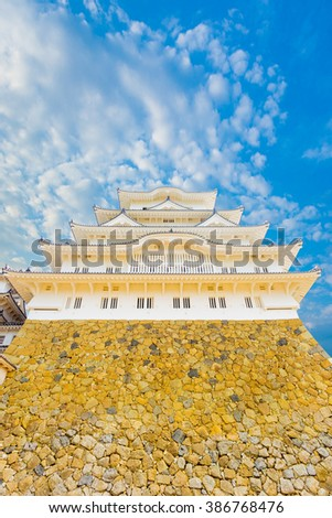 Below the main stronghold of Himeji-jo castle looking directly up from the base on a clear blue sky day in Himeji, Japan after 2015 renovations. Vertical copy space