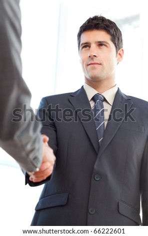 Below view of a serious businessman concluding a deal with a partner at the office - stock photo