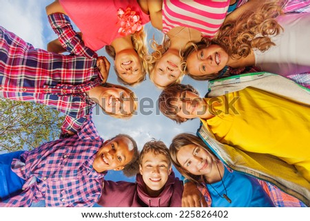Below view of children standing in circle form - stock photo