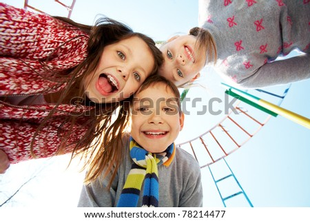Below view of happy children looking and smiling at camera - stock photo