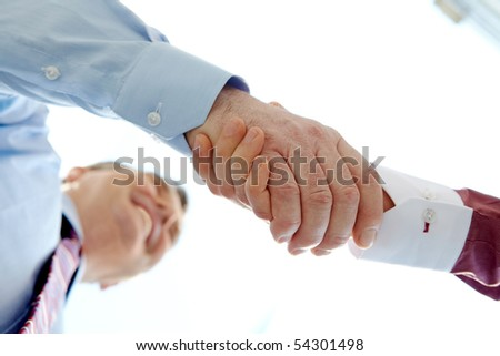 Below view of happy senior chief handshaking outdoors with partner - stock photo
