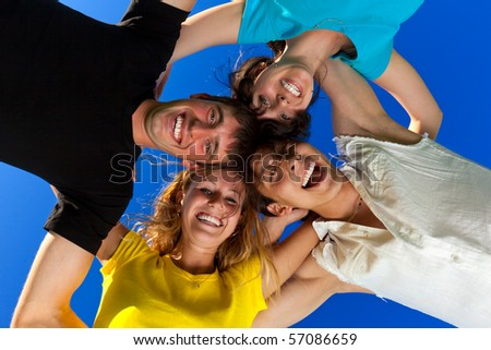 Below view of joyful teens embracing and looking at camera with smiles - stock photo