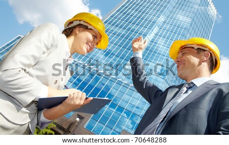 Below view of pretty woman interviewing architect - stock photo