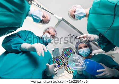 Below view of surgeons holding medical instruments in hands and looking at patient