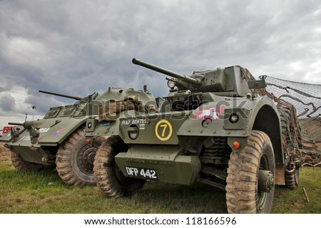 BELTRING, UK - JULY 19: A pair of ex British Army armoured reconnaissance vehicles sit under camouflaged netting and stormy skies at the War & Peace military show on July 19, 2012 in Beltring - stock photo
