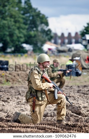 BELTRING, UK - JULY 19: A re-enactor dressed in Russian army uniform prepares to attack a dummy wooden house occupied by Afgan re-enactors at the War & Peace show on July 19, 2012 at Beltring