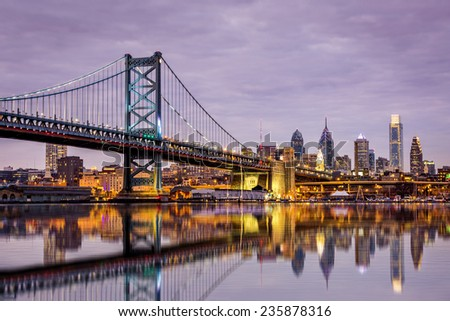 Ben Franklin bridge and Philadelphia skyline reflected in the Delaware river under a purple twilight - stock photo