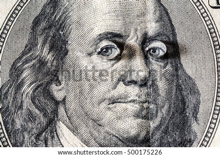 Ben Franklin's face with drops of water on eyes on the old US $100 dollar bill macro.