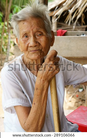 BEN TRE, VIET NAM- JUNE 2: Asian old woman with stick walking at Vietnamese countryside, senior very healthy walking on path, female usually have long living, Bentre, Vietnam, June 2, 2015