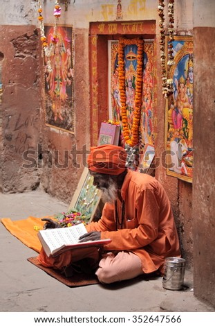 BENARES, VARANASI UTTAR PRADESH, INDIA - FEBRUARY 13, 2013: Hindu devotee reads and reciting sacred texts