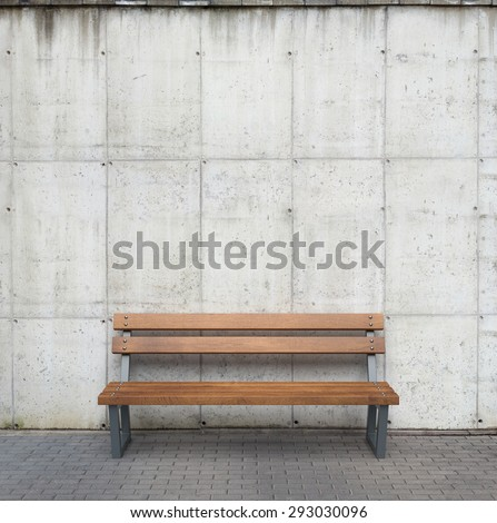 Bench against concrete wall - stock photo