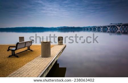Bench along the Potomac River, in Alexandria, Virginia. - stock photo