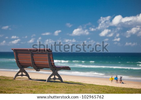 Bench by the beach with surfers in background, Surfers Paradise, Gold Coast, Queensland, Australia - stock photo