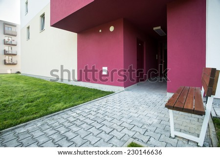 Bench in front of block of flats - stock photo