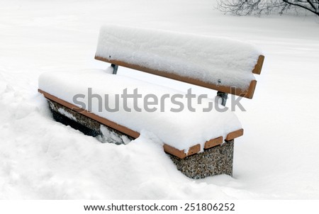 Bench in park covered snow - stock photo