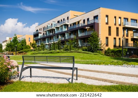 Bench in public park with modern block of flats in the background - stock photo
