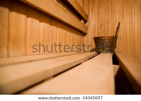 Bench in sauna and copper bucket