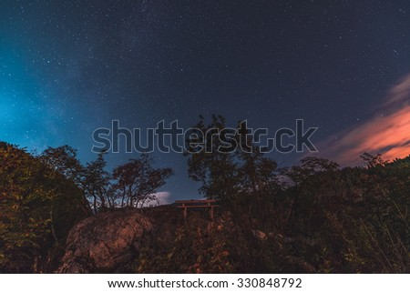 Bench in the forest under a starry night. Taken at Ojstrica view point above lake Bled - stock photo