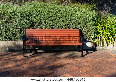 Bench in the garden on a sunny day with green hedge on the background. Urban park landscape - stock photo
