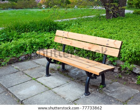 Bench in the spring park - stock photo