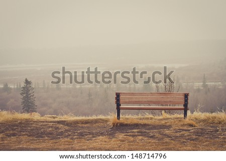 Bench looking over a misty landscape - stock photo