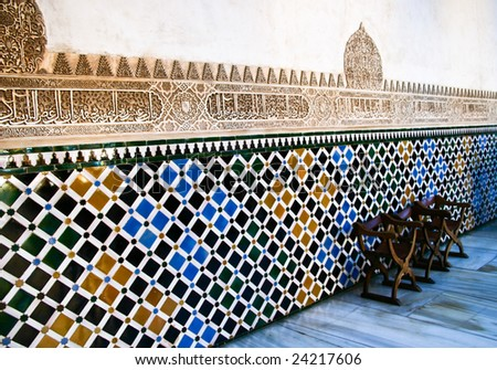 Bench next to mosaic wall in the Court of the Myrtles (Patio de los Arrayanes) Alhambra Palace Granada Spain. It is also called Patio of the Pond or the Reservoir (Patio del Estanque o de la Alberca) - stock photo