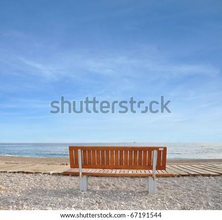 Bench on Rocky Vacation Beach in Mediterranean Europe City Villa Joyosa Costa Blanca Alicante Spain - stock photo