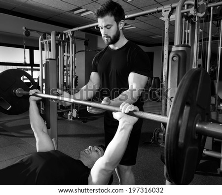 Bench press weightlifting man with personal trainer in fitness gym - stock photo