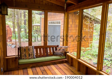 Bench swing hung by chain looking comfortable on a screened in porch. - stock photo