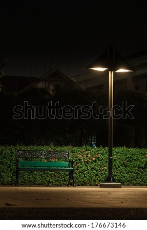 Bench under a lamp In the park alone at night. - stock photo