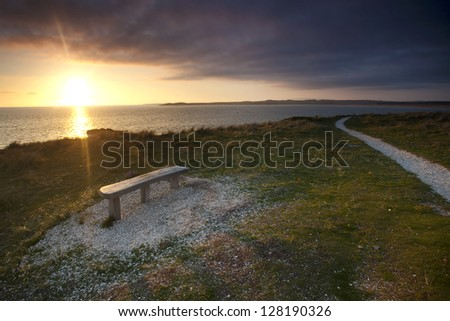bench view out to sea at sunset - stock photo