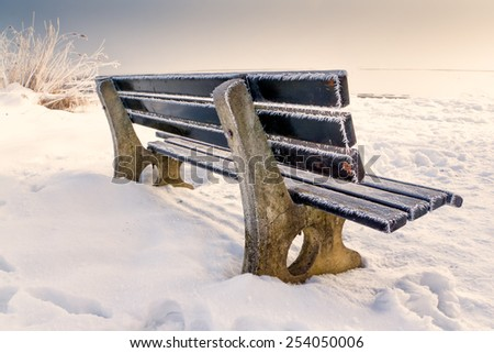bench with ice on snowy winter day - stock photo