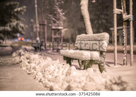 bench with snow after snowstorm or in snow calamity in europe, winter night  photography in city - stock photo