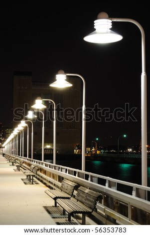 Benches and lamp posts on a pier at night. - stock photo