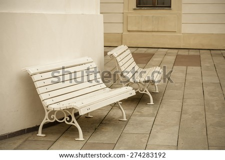Benches, standing near to the building, peaceful resting place. - stock photo