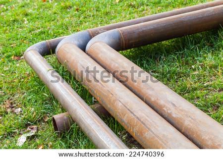 Bend of industrial outdoor steel pipeline over green grass - stock photo