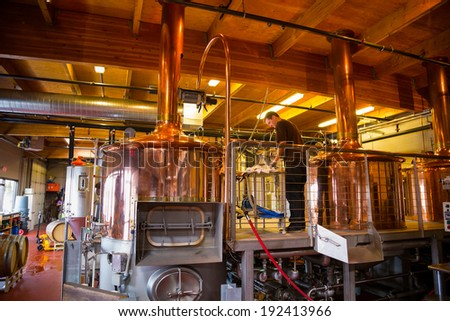 BEND, OR - JANUARY 12, 2014: Beer making inside of the Crux Fermentation Project with large fermenters and industrial equipment. - stock photo