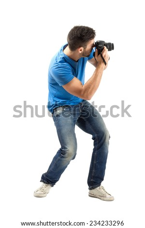 Bend young man taking photo with digital camera side view. Full body length portrait isolated over white background. - stock photo