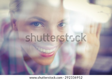 Bended pretty woman looking through the glass in the bakery - stock photo