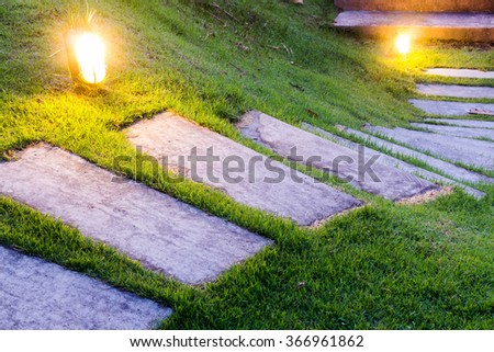 Bending garden stone path at night with glowing light from garden outdoor light - stock photo